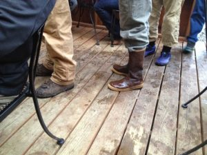 Image of the boots of several people standing in line