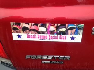 "Image of a bumper sticker showing several womens' behinds and reading, ""Denalie Dames Social Club Talkeetna, Alaska"""