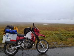 Image of a red motorcycle parked with gorgeous and colorful tundra in the background