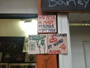 "Image of signs posted to a pole reading, ""How beer is made, thunder + hop magic. Delivered by wizard aliens"""