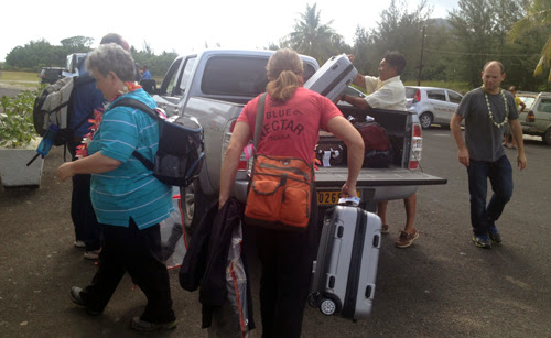 Image of several people unloading a collecting baggage from the back of a truck