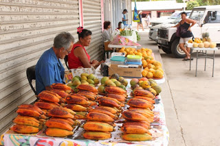 Image of a local outside market with several tables piled high with fresh fruit