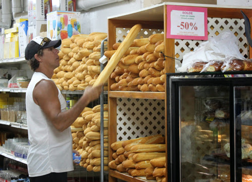 Image a shopper at a store selected a baguette from a shelf of breads