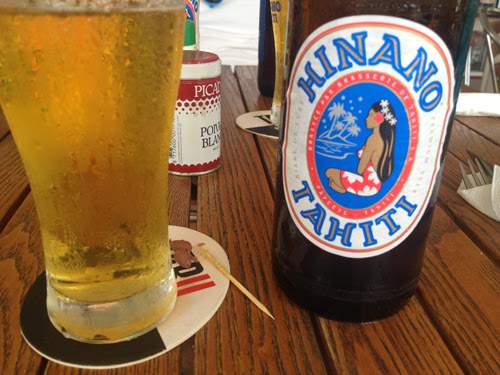 "Image of a beer in a glass next to the bottle reading, ""Hinano Tahiti"""