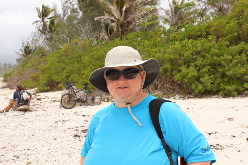 Image of a woman (Marla) on the beach, wearing a hat and blue shirt while smiling