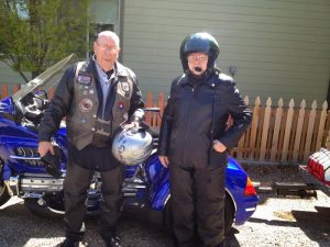 Image of Gene and Arlene posing in full motorcycle attire in front of a bike
