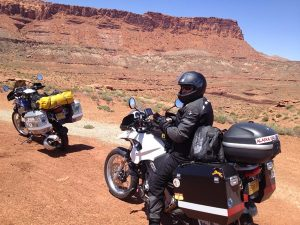Image of Michael sitting on Judy\s motorcycle with the Valley of the Gods in the background
