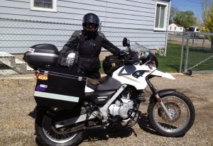 Image of Judy in full motorcycle attire standing in front of her packed bike