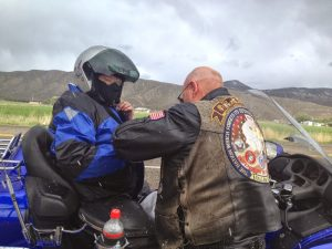 Image of Gene helping a fully attired Arlene zip up her motorcycle jacket while she sits on a bike