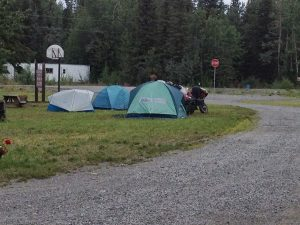 Image of several tents, with a motorcycle park outside one, in a green patch along side a dirt road