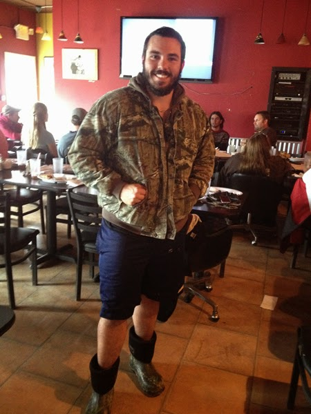 Man wearing boots, shorts, and a camo jacket
