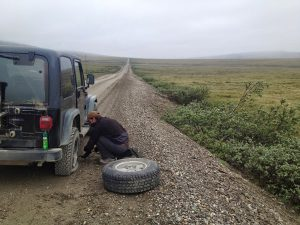 Image of Michael changing the tire on the Jeep