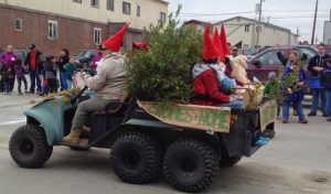 Image of people sitting on a four-wheeler wearing gnome costumes and riding through the parade