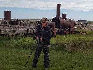 Judy standing in a marsh with a tripod in front of an old train