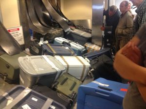 Image of a pile of suitcases in disarray and many people standing on the outskirts trying to find their luggage