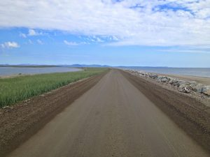 Image of a long dirt road with water in the background