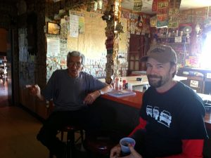 Image of Michael sitting at a bar with another man (Tom)