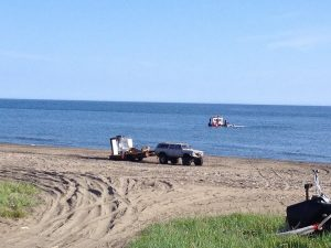 Image of a truck pulling a dredge-like contraption across the beach