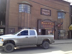 "Image of a white truck with a broken window parked in front of a building with a sign reading, ""Board of Trade Saloon"""