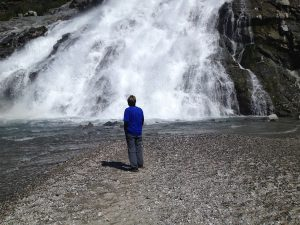 Image of Judy standing in front of a massive waterfall
