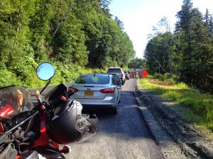 Image of a motorcycle stuck behind a long line of cars waiting for a pilot vehicle
