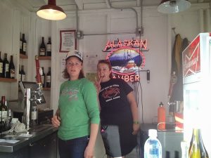 "Image of two women serving beer with a neon sign behind them reading, ""Alaskan Amber"""