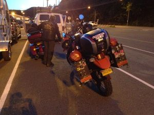 Image of Judy's motorcycle parked behind Jaz and her bike behind several parked cars