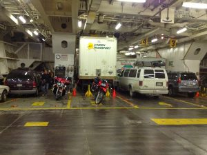 Image of two motorcycles parked behind several large vehicles inside a ferry on deck