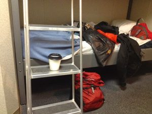 Image of a small sleeping area with Judy's bags spread out and a cup of coffee on the ladder to the top bunk