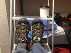 Image of Judy's shoes resting on the ladder to the top bunk, with a cup of coffee on the ladder