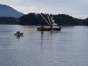 Image of a boat in the water surrounded by a net next to a smaller boat with a fisherman standing in it