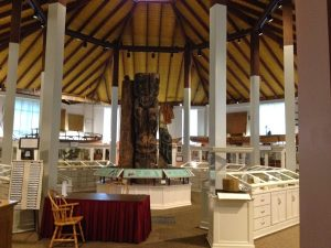 Image of the center of the Sheldon Jackson Museum with three totem pole artifacts