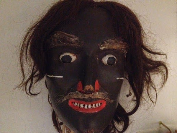 Image of a black faced mask with large eyes and showing white teeth