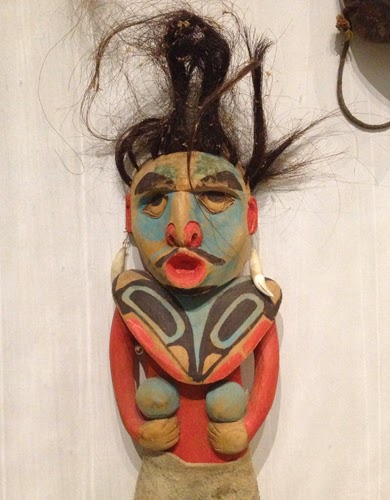 Image of a wooden painted doll with crazy black hair