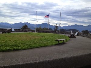 Image of the top of Castle Hill; a large open grassy area with park benches and an American flag with cannons