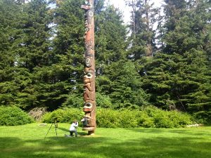 Image of a tall totem pole with a Judy kneeling to take a picture of it