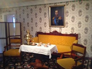Image of an old fashioned-looking living room with a bright yellow couch, a picture of a man hanging behind, and a table with gold or brass dishes