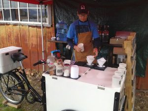 Image of a man serving coffee out of a bike cart