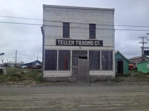 "Image of a simple building with a sign in front reading, ""Teller Trading Co"""
