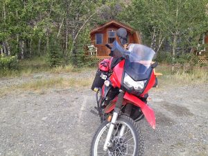 Image of a motorcycle parked in front of a wooden cabin