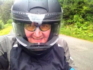 Image of Judy wearing a motorcycle helmet and smiling
