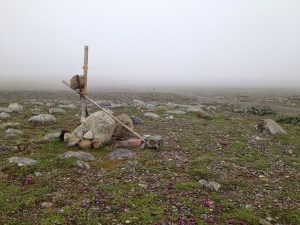 Image of some rocks and sticks placed together to represent a road marker